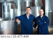 Купить «Two friendly men in uniforms standing in winery fermentation compartment», фото № 29477444, снято 13 декабря 2019 г. (c) Яков Филимонов / Фотобанк Лори