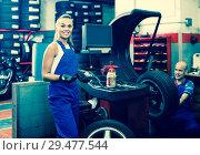 Купить «female technician standing with wheel balancing machinery at auto workshop», фото № 29477544, снято 19 сентября 2019 г. (c) Яков Филимонов / Фотобанк Лори