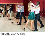 Купить «Positive adult couples dancing tango together in modern studio», фото № 29477556, снято 4 октября 2018 г. (c) Яков Филимонов / Фотобанк Лори