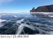 Купить «Lake Baikal. Beautiful blue ice with cracks near the famous Cape Khoboy of the Olkhon Island. On the horizon is visible a group of tourists near the rocks», фото № 29484964, снято 8 марта 2015 г. (c) Виктория Катьянова / Фотобанк Лори