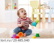 Купить «Baby toddler boy playing indoors with developmental toy sitting on soft carpet», фото № 29485040, снято 16 декабря 2018 г. (c) Оксана Кузьмина / Фотобанк Лори