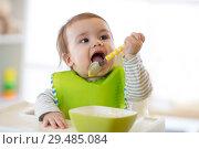 Купить «Happy infant baby boy spoon eats itself», фото № 29485084, снято 30 мая 2020 г. (c) Оксана Кузьмина / Фотобанк Лори