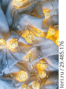 Купить «A garland background with ball lights on the folds of fabric in light gray. Copy space», фото № 29485176, снято 17 января 2018 г. (c) Tetiana Chugunova / Фотобанк Лори