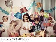 Купить «Boys and girls handing gifts to each other during dinner», фото № 29485260, снято 26 июня 2019 г. (c) Яков Филимонов / Фотобанк Лори