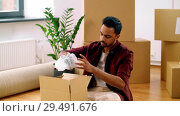 Купить «indian man packing boxes and moving to new home», видеоролик № 29491676, снято 23 мая 2019 г. (c) Syda Productions / Фотобанк Лори