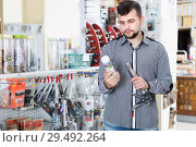 Купить «Male choosing new glue in houseware shop», фото № 29492264, снято 5 апреля 2017 г. (c) Яков Филимонов / Фотобанк Лори