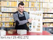 Купить «Adult male seller demonstrating assortment», фото № 29492272, снято 5 апреля 2017 г. (c) Яков Филимонов / Фотобанк Лори