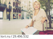 Купить «Adult woman 50-60 years old is sitting with map and suitcase», фото № 29496532, снято 3 сентября 2017 г. (c) Яков Филимонов / Фотобанк Лори