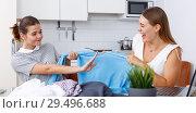Купить «Emotinal women holding blue jacket and having conflict about sharing», фото № 29496688, снято 2 августа 2018 г. (c) Яков Филимонов / Фотобанк Лори