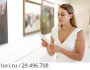 Купить «Woman visiting painting exhibition», фото № 29496708, снято 28 июля 2018 г. (c) Яков Филимонов / Фотобанк Лори