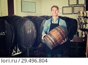 Купить «Man in apron having wood with wine in hands», фото № 29496804, снято 20 мая 2019 г. (c) Яков Филимонов / Фотобанк Лори