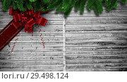 Купить «Video composition with snow over Christmas gift  ribbon on wood», видеоролик № 29498124, снято 13 декабря 2018 г. (c) Wavebreak Media / Фотобанк Лори