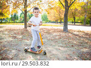 Купить «Playful boy on a scooter», фото № 29503832, снято 25 сентября 2015 г. (c) Сергей Сухоруков / Фотобанк Лори