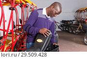 Купить «Driver of pedicab inspecting luggage basket», фото № 29509428, снято 22 мая 2018 г. (c) Яков Филимонов / Фотобанк Лори