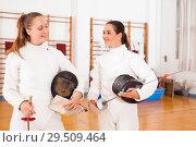 Купить «Active young women fencers in uniform talking at fencing room», фото № 29509464, снято 11 июля 2018 г. (c) Яков Филимонов / Фотобанк Лори
