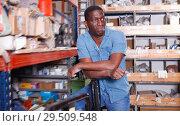 Купить «Portrait of confident African American man standing among shelves with materials for renovation works», фото № 29509548, снято 12 апреля 2018 г. (c) Яков Филимонов / Фотобанк Лори