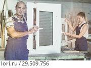Купить «Workman in blue overalls demonstrating pvc window», фото № 29509756, снято 19 июля 2017 г. (c) Яков Филимонов / Фотобанк Лори
