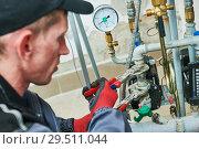 Купить «heating engineer or plumber in boiler room installing or adjusting pipeline», фото № 29511044, снято 5 октября 2018 г. (c) Дмитрий Калиновский / Фотобанк Лори