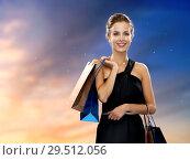 Купить «happy woman in black dress with shopping bags», фото № 29512056, снято 1 июня 2014 г. (c) Syda Productions / Фотобанк Лори