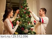 Купить «happy couple decorating christmas tree at home», фото № 29512096, снято 11 января 2018 г. (c) Syda Productions / Фотобанк Лори