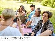 Купить «friends photographing at picnic in summer park», фото № 29512132, снято 17 июня 2018 г. (c) Syda Productions / Фотобанк Лори