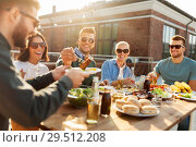 Купить «friends having dinner or bbq party on rooftop», фото № 29512208, снято 2 сентября 2018 г. (c) Syda Productions / Фотобанк Лори