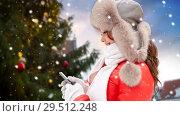 Купить «woman with smartphone over christmas tree», фото № 29512248, снято 7 января 2017 г. (c) Syda Productions / Фотобанк Лори