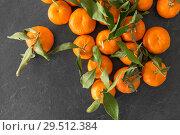 Купить «close up of mandarins on slate table top», фото № 29512384, снято 4 апреля 2018 г. (c) Syda Productions / Фотобанк Лори