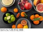 Купить «close up of citrus in bowls fruits on stone table», фото № 29512388, снято 4 апреля 2018 г. (c) Syda Productions / Фотобанк Лори