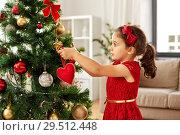 Купить «little girl decorating christmas tree at home», фото № 29512448, снято 29 августа 2018 г. (c) Syda Productions / Фотобанк Лори