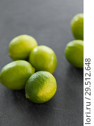 Купить «close up of whole limes on slate table top», фото № 29512648, снято 4 апреля 2018 г. (c) Syda Productions / Фотобанк Лори