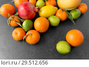 Купить «close up of citrus fruits on stone table», фото № 29512656, снято 4 апреля 2018 г. (c) Syda Productions / Фотобанк Лори
