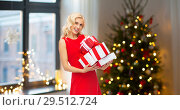 Купить «happy woman in red dress with christmas gifts», фото № 29512724, снято 3 октября 2015 г. (c) Syda Productions / Фотобанк Лори