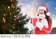 Купить «happy woman with gift over christmas tree», фото № 29512956, снято 7 января 2017 г. (c) Syda Productions / Фотобанк Лори