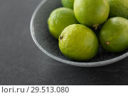 Купить «close up of whole limes in bowl on slate table top», фото № 29513080, снято 4 апреля 2018 г. (c) Syda Productions / Фотобанк Лори