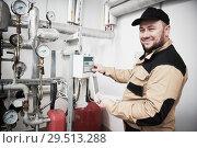 Купить «heating engineer or plumber inspector in boiler room taking readouts or adjusting meter», фото № 29513288, снято 5 октября 2018 г. (c) Дмитрий Калиновский / Фотобанк Лори