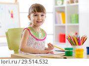 Купить «Cute little girl is drawing with pencils in preschool», фото № 29514532, снято 5 июля 2020 г. (c) Оксана Кузьмина / Фотобанк Лори