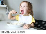 Купить «Happy cute little girl eats quark on kitchen», фото № 29516060, снято 30 октября 2018 г. (c) ivolodina / Фотобанк Лори
