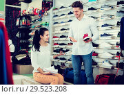 Купить «Positive seller demonstrating sneakers to female», фото № 29523208, снято 22 ноября 2016 г. (c) Яков Филимонов / Фотобанк Лори