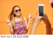 Купить «teenage girl photographing friend by smartphone», фото № 29523688, снято 19 июля 2018 г. (c) Syda Productions / Фотобанк Лори