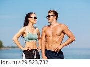 Купить «happy couple in sports clothes and shades on beach», фото № 29523732, снято 1 августа 2018 г. (c) Syda Productions / Фотобанк Лори