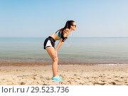 Купить «female runner with earphones and arm band on beach», фото № 29523736, снято 1 августа 2018 г. (c) Syda Productions / Фотобанк Лори