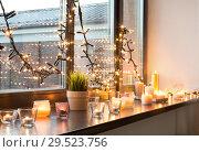 Купить «candles burning on window sill with garland lights», фото № 29523756, снято 13 января 2018 г. (c) Syda Productions / Фотобанк Лори