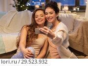 Купить «female friends taking selfie by smartphone at home», фото № 29523932, снято 21 января 2018 г. (c) Syda Productions / Фотобанк Лори