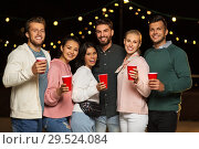 Купить «friends with party cups on rooftop at night», фото № 29524084, снято 2 сентября 2018 г. (c) Syda Productions / Фотобанк Лори