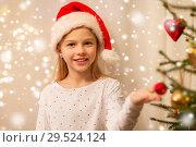Купить «happy girl in santa hat decorating christmas tree», фото № 29524124, снято 22 декабря 2017 г. (c) Syda Productions / Фотобанк Лори