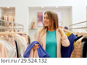 Купить «happy young woman choosing clothes in mall», фото № 29524132, снято 19 февраля 2016 г. (c) Syda Productions / Фотобанк Лори
