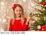 Купить «happy girl in red decorating christmas tree», фото № 29524188, снято 22 декабря 2017 г. (c) Syda Productions / Фотобанк Лори