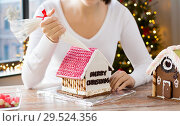 Купить «woman making gingerbread house on christmas», фото № 29524356, снято 30 октября 2014 г. (c) Syda Productions / Фотобанк Лори