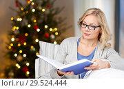Купить «woman in glasses reading book on christmas», фото № 29524444, снято 27 ноября 2015 г. (c) Syda Productions / Фотобанк Лори